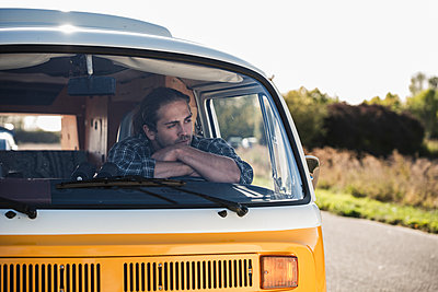 Young man on a road trip with his camper, taking a break, relaxing - p300m2069749 by Uwe Umstätter