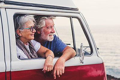 Senior couple traveling in a vintage van, looking at the sea - p300m2114886 by Simona Pilolla