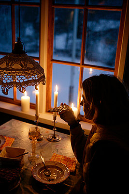 Woman eating dinner in restaurant with candles burning in background - p312m799342f by Per Eriksson