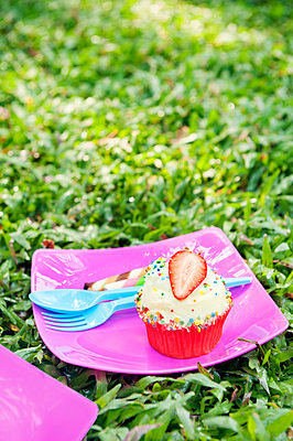 Strawberry cupcake at birthday picnic - p352m2039885 by Anna Larsson