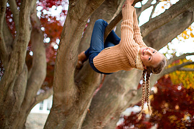 Low angle view of smiling girl climbing tree - p555m1409476 by Shestock