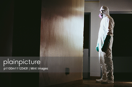 Man wearing a hazardous material protective clean suit, facing bright light in hallway - p1100m1112343f by Mint Images