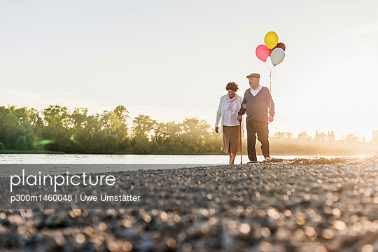 Senior couple with balloons strolling at riverside - p300m1460048 by Uwe Umstätter