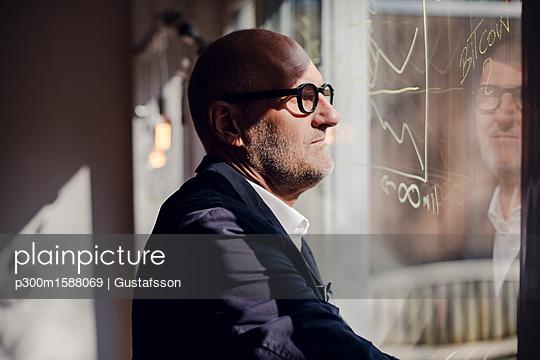senior businessman brainstorming, drawing formulas on window pane - p300m1588069 von Gustafsson