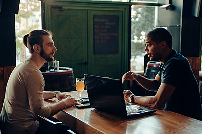 Two men with laptop sitting in a bar talking - p300m1101079f by Zeljko Dangubic
