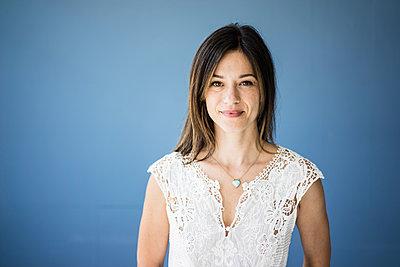 Portrait of a beautiful woman against blue background - p300m2069286 von Robijn Page