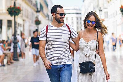 Spain, Andalusia, Malaga, happy tourist couple walking in the city - p300m2070455 von Javier Sánchez Mingorance