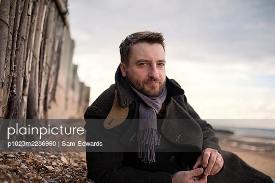 Portrait confident handsome man in winter coat on beach - p1023m2286990 by Sam Edwards