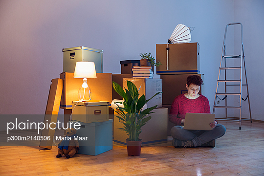 Woman using laptop surrounded by cardboard boxes in a new home - p300m2140596 by Maria Maar