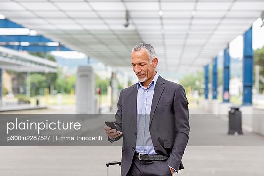 Senior business man in suit near train platform; Florence, Italy - p300m2287527 von Emma Innocenti