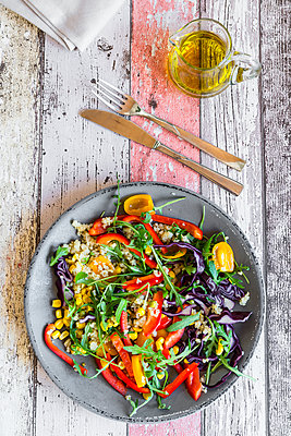 Glass of rainbow salad with bulgur, rocket and different vegetables and bowls with ingredients - p300m1356056 by Sandra Roesch
