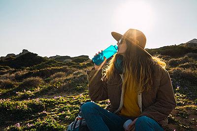 Italy, Sardinia, woman on a hiking trip having a break drinking from water bottle - p300m1581139 von Kike Arnaiz