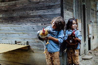 Two kids holding chickens on an organic farm - p300m2144424 von Sofie Delauw