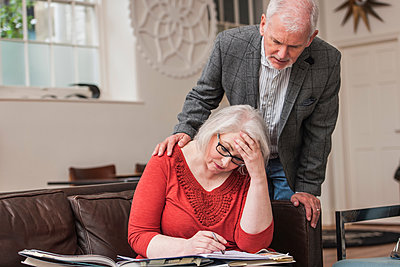 Senior man comforting woman on couch - p429m1207033 by Colin Hawkins