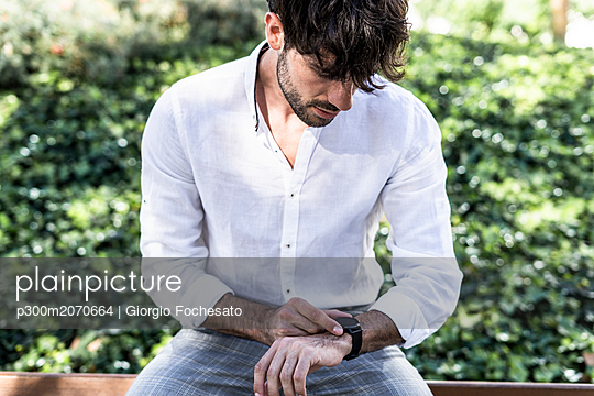 Young man sitting outdoors using smartwatch - p300m2070664 by Giorgio Fochesato