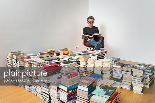 Mann sitzt zwischen vielen Büchern - p305m1586705 von Dirk Morla