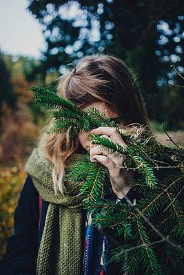 Junge Frau versteckt sich hinter Fichte - p1184m1091938 von brabanski