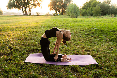 Young woman practicing yoga in park - p1427m2085234 by Mykhailo Lukashuk