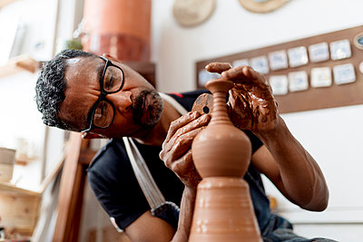 Close-up of male artist making earthenware while sitting in workshop - p300m2213992 by Ezequiel Giménez