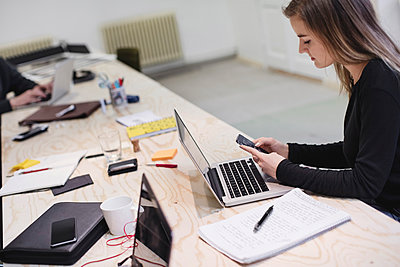 Young woman using smart phone at desk in creative office - p426m1407195 by Maskot
