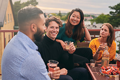 Cheerful friends enjoying social gathering on terrace during sunset - p426m2074297 by Maskot