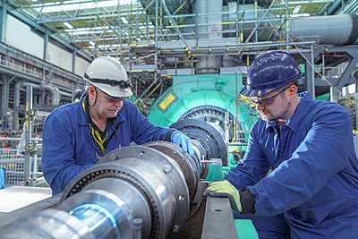 Engineers inspecting gears at generator end in nuclear power station during outage - p429m2058278 by Monty Rakusen
