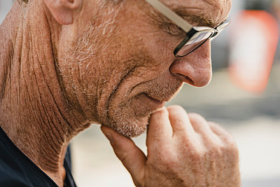 Mature man with chin resting on hand - p586m2109104 by Kniel Synnatzschke