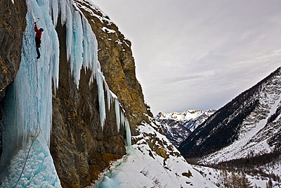 An ice climber ascending a frozen cascade in the Fournel Valley, Ecrins Massif, France, Europe - p8713171 by David Pickford