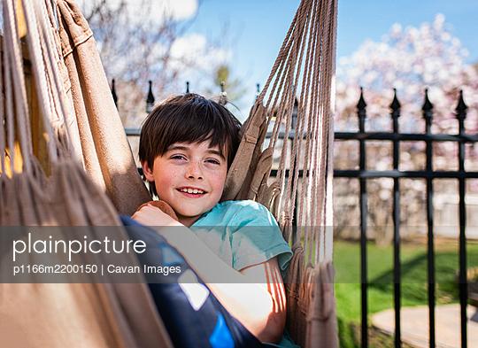 Happy boy relaxing in a hammock in a backyard on a summer day. - p1166m2200150 by Cavan Images