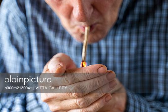 Senior man at home smoking marihuana joint - p300m2139941 by VITTA GALLERY