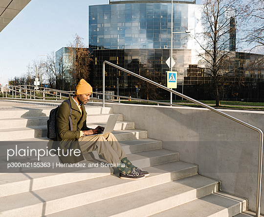 Stylish man using laptop outside of the office - p300m2155363 by Hernandez and Sorokina