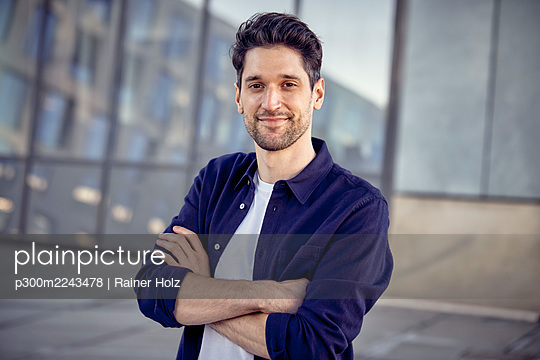 Male entrepreneur standing with arms crossed outdoors - p300m2243478 by Rainer Holz