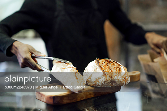 Salesman packing fresh bread while working at bakery - p300m2243973 by Miguel Angel Partido Garcia