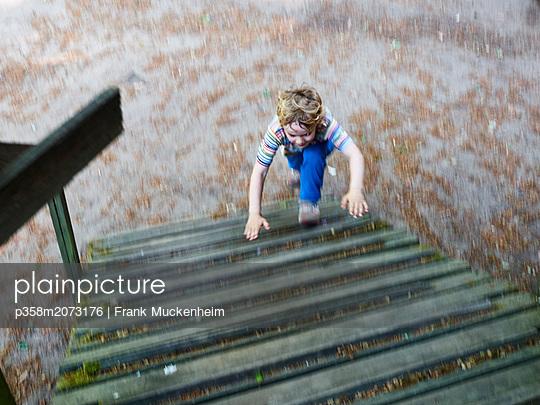 Kleiner Junge rennt Holztreppe hoch - p358m2073176 von Frank Muckenheim