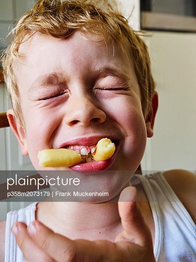 Kleiner Junge ißt Schupfnudeln - p358m2073179 von Frank Muckenheim