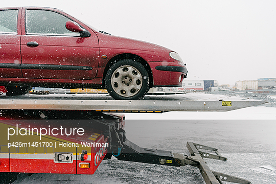 Damaged maroon car on tow truck against sky during winter - p426m1451700 by Helena Wahlman
