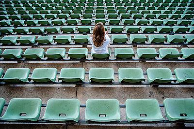 Single woman on tribune in football stadium, Friedrich-Ludwig-Jahn-Sportpark - p1093m2193637 by Sven Hagolani