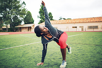 Determined female athlete doing stretching exercise on field - p1166m1086164f by John Trice
