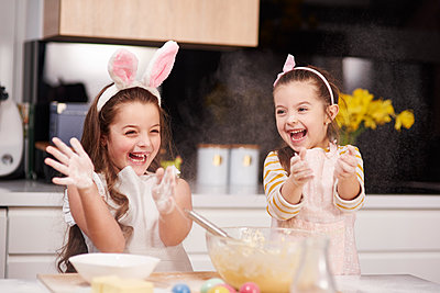 Two playful sisters having fun baking Easter cookies in kitchen together - p300m1567652 by gpointstudio
