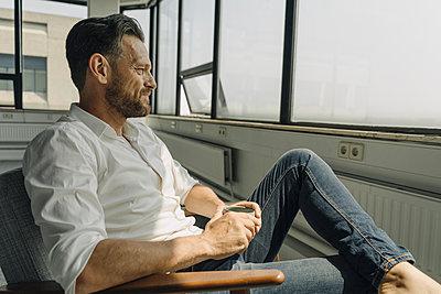 Mature businessman with cup of coffee sitting in armchair in empty office - p300m2155469 von Kniel Synnatzschke