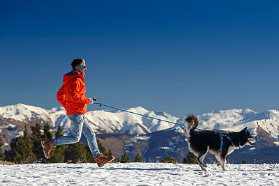 Man running with dog in snow covered mountain landscape - p429m1407845 by Quim Roser
