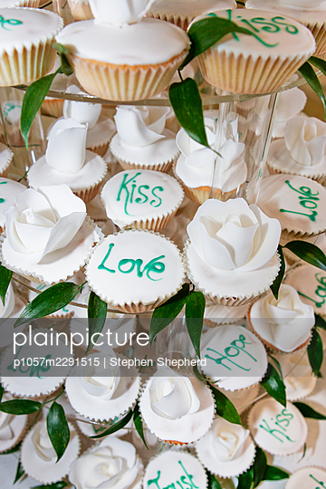 A large tower of mini fairy cakes at a wedding making up one single wedding cake. - p1057m2291515 by Stephen Shepherd