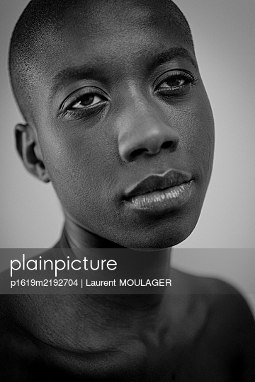 Portrait of a young black woman with shaved hair - p1619m2192704 by Laurent MOULAGER