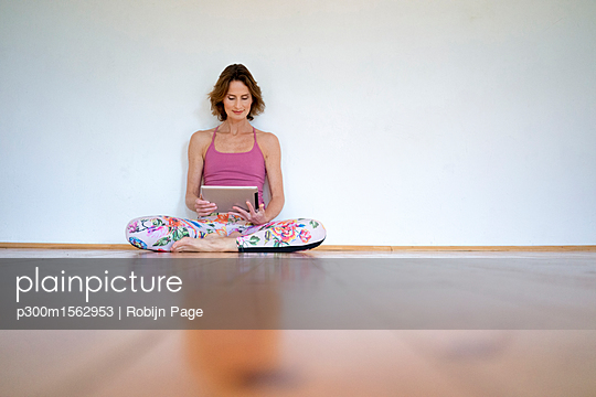 Mature woman sitting on floor in empty room using tablet - p300m1562953 by Robijn Page