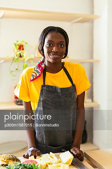 Portrait of smiling woman in kitchen - p300m1587015 von Bonninstudio