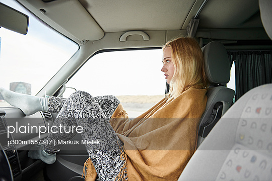 Blond young woman sitting in car looking at distance - p300m1587347 von Markus Mielek