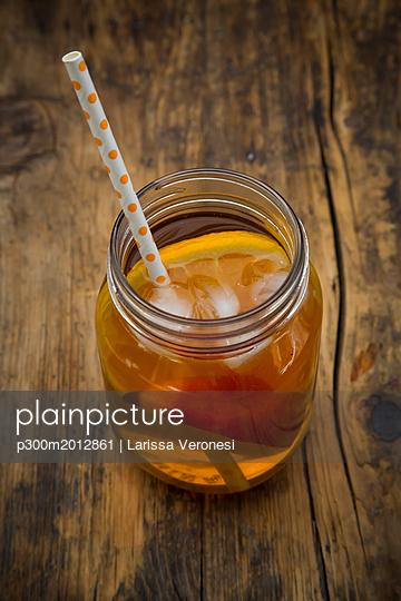 Glass of peach orange ice tea on wood - p300m2012861 von Larissa Veronesi