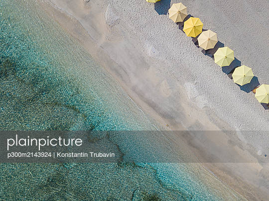 Drone shot of yellow parasols arranged at beach in Bali, Indonesia - p300m2143924 by Konstantin Trubavin