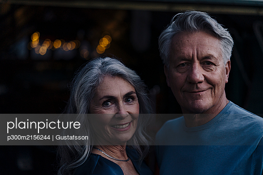 Portrait of a smiling senior couple outdoors at night - p300m2156244 by Gustafsson