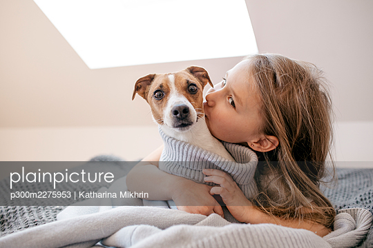 Cute girl embracing dog at home - p300m2275953 by Katharina Mikhrin